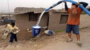 """A distributor of potable water fills a cylinder in """"Pachacutec's"""" shanty town, north of Lima, 26 December 2005. According to the committee """"Peruvians Without Water"""", 2 million residents of Lima and 7 million of Peruvians lack of a sewer system of potable water from Peru's state-owned water utility SEDAPAL (Serice of Sewer System and Potable Water of Lima) and 3,500 children die every year because of this shortage. Lima is considered one of the cities with higher population density in deserted areas, where the price of water is higher than in the areas with the regular system, according to the United Nations program for the environment. AFP PHOTO/EITAN ABRAMOVICH OPSE 2006ENE05 PERU ASENTAMIENTO HUMANO PACHACUTEC DISTRIBUCION AGUA CAMION CISTERNA 2006ENE05 AFD"""